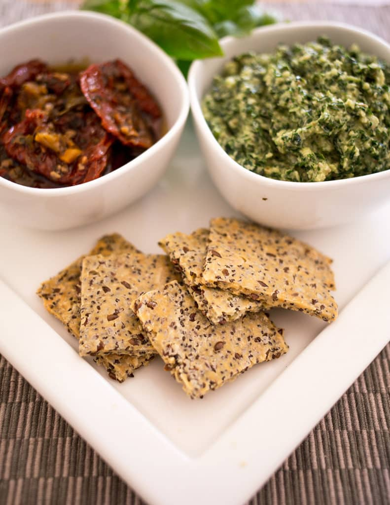 Seed crackers on platter with some pesto and sundried tomatoes