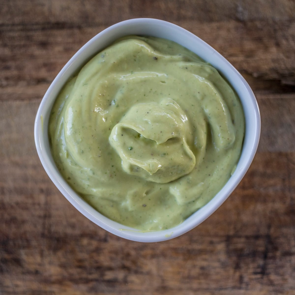 Avocado sauce in white bowl on wooden backrgound.