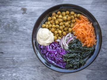 Birds eye view of spicy chickpea buddha bowl in black bowl on a wooden background.