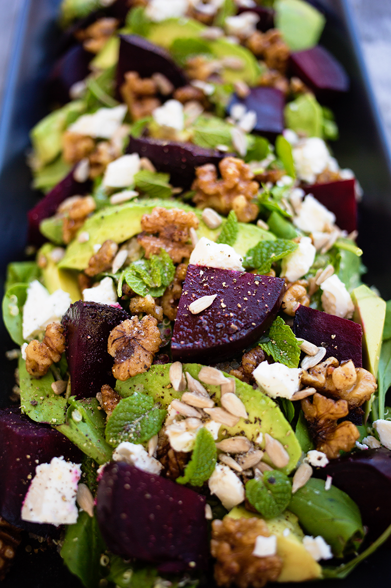 Close up of beetroot and avocado salad highlighting sunflowerseeds, walnuts and mint.