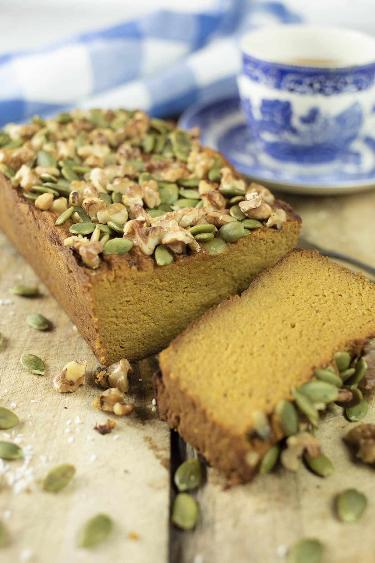 Close up of Paleo pumpkin bread with a slice cut on chopping board with cup and saucer behind with tea.