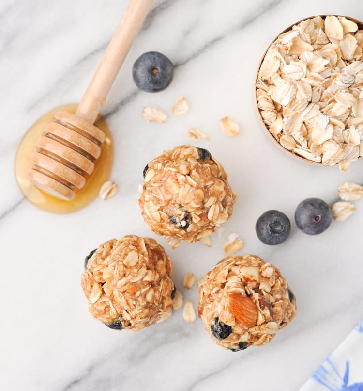 No-Bake Almond Blueberry Snacks on marble background with honey, oats and blueberries in background.