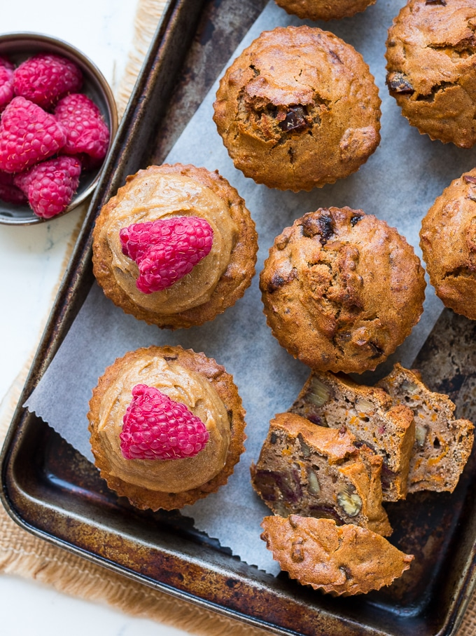 Buckwheat, carrot, date and walnut muffins on baking tray some with raspberries on top with raspberries in a bowl to the side.