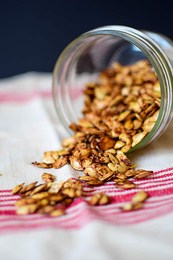 Roasted pumpkin seeds spilling out of a jar on white and red cloth.