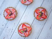 Four mini strawberry tarts on white table.