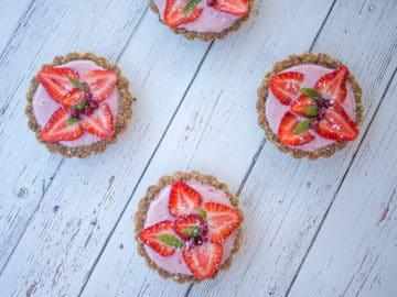 Four mini strawberry tarts on white table.