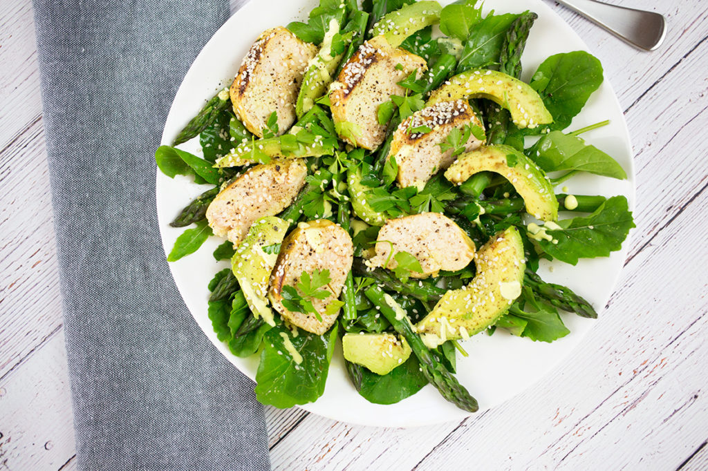 Birdseye view of chicken, avocado and asparagus salad on white background with grey napkin