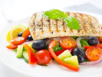 Close up of greek fish salad with glass of water