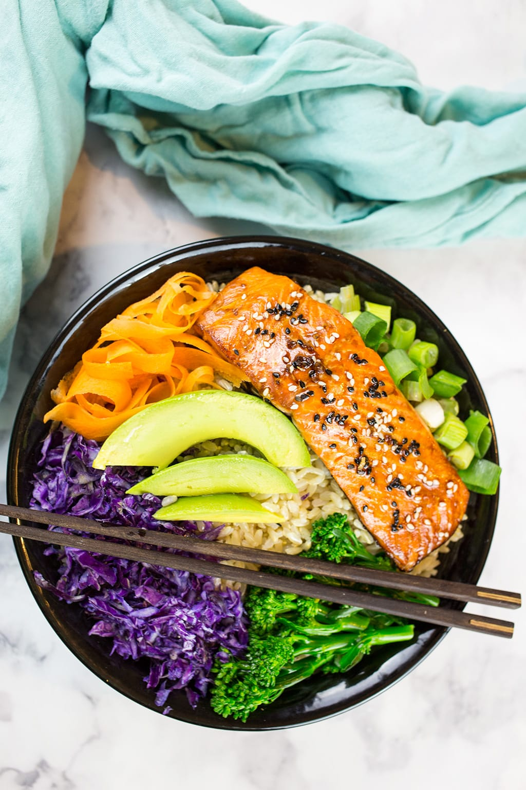 Teriyaki Salmon Bowl Birds Eye View in black bowl with green cloth in the background.