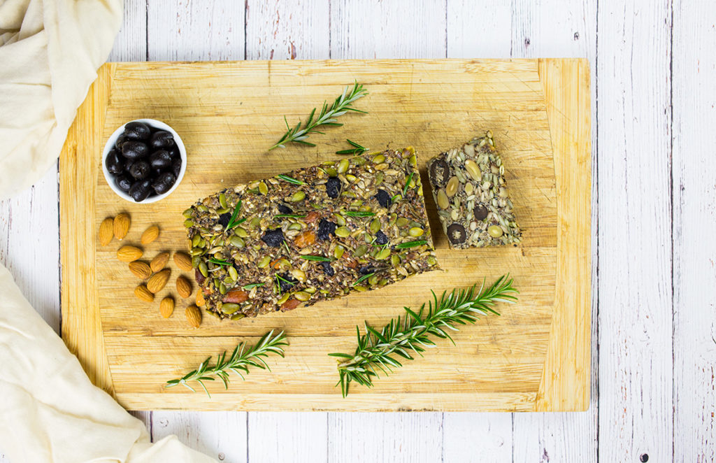 Paleo Nut and Seed Bread on chopping board with rosemary sprigs, bowl of olives and almonds beside it on white background.