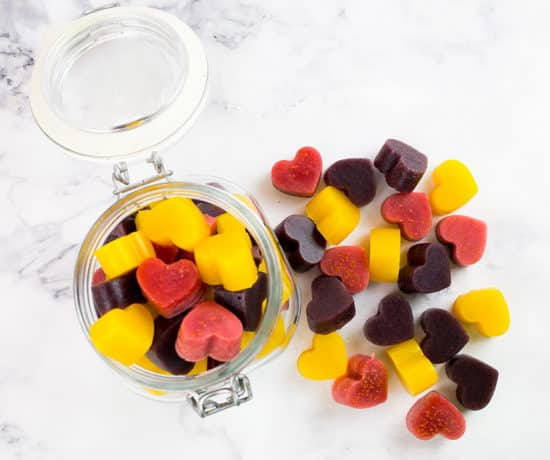 Three types of heart shaped gummies in a jar and outside of jar.