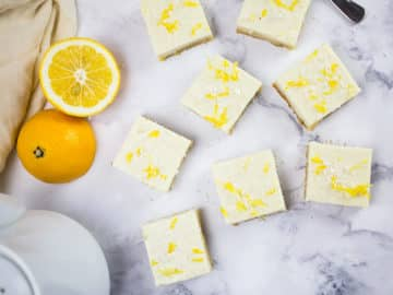 Birds eye view of creamy lemon squares on marble background with teapot and sliced lemon to the side.