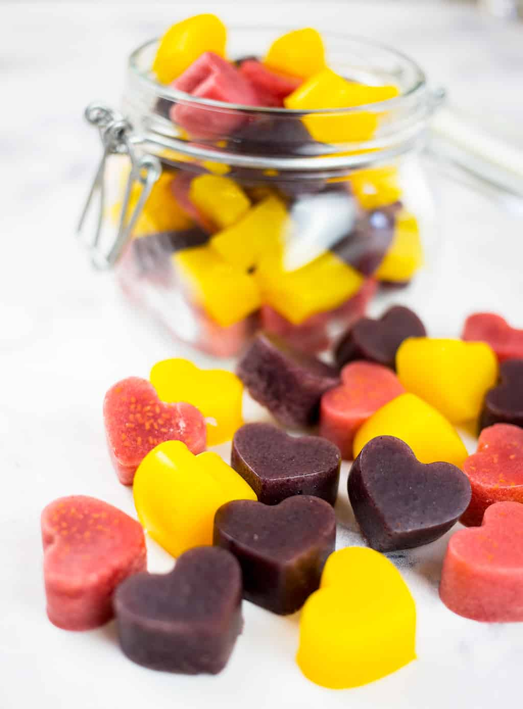 Mango gummies, raspberry gummies and blueberry gummies spilling out of glas jar on white background.