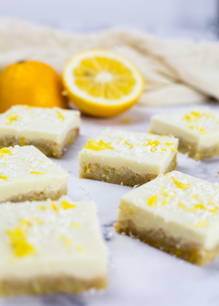Close up of lemon squares with sliced lemon and beige cloth in the background.