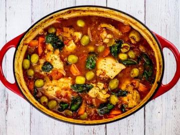 Birdseye view of Spanish chicken stew in red dish on white background.