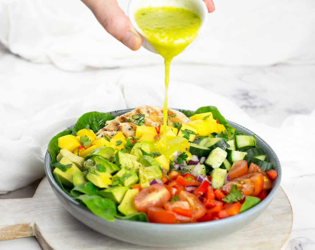 Chicken Mango Salad with Mango Cilantro Dressing pouring over it