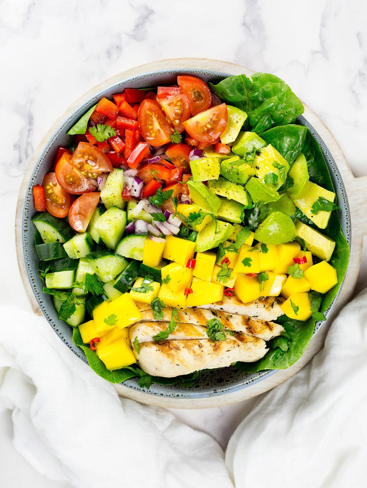 Birdseye view of chicken mango salad inblue/grey dish on white background.
