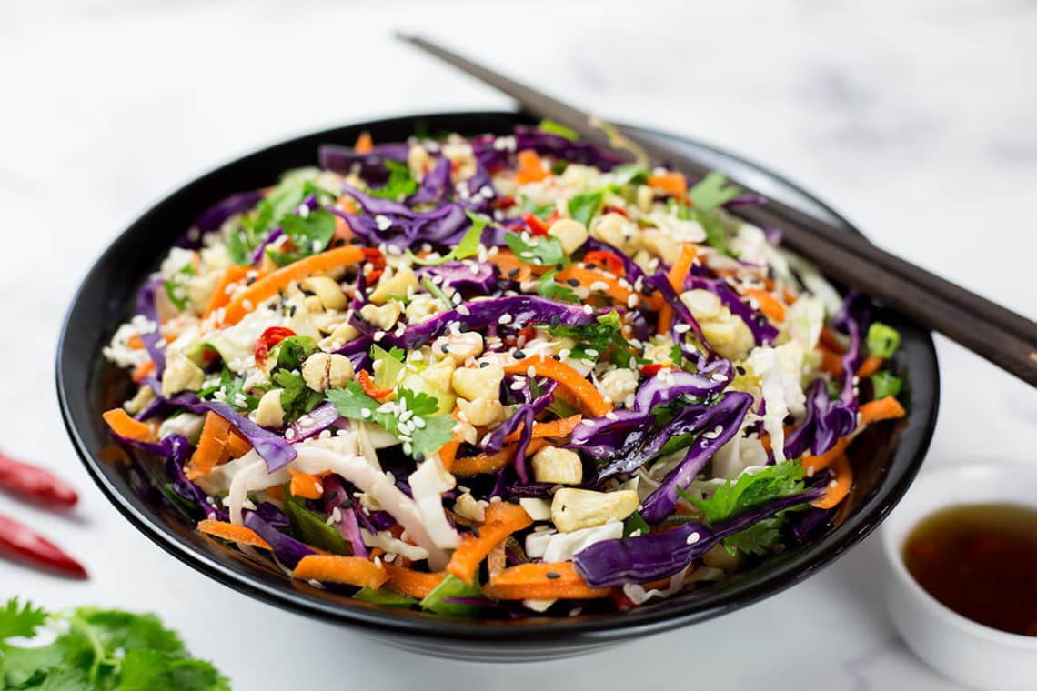Asian slaw in black bowl with asian style dressing, chillis and coriander beside it on a white background.