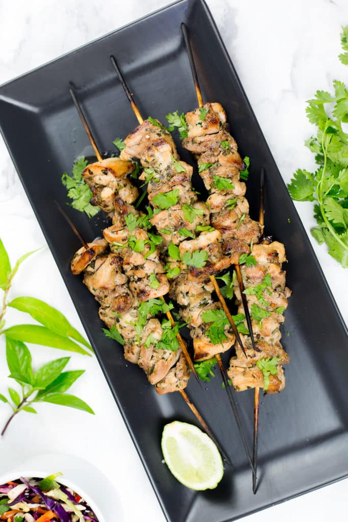 Birds eye view of chicken skewers with side salad and coriander