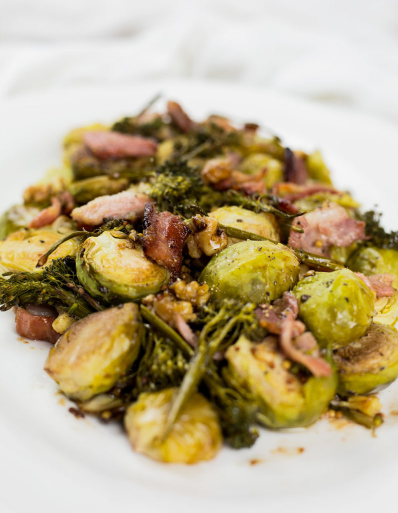 Close up of roasted brussels sprouts with bacon on a plate