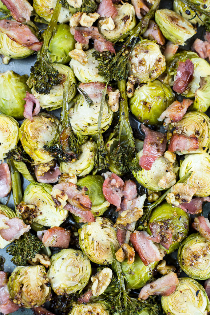 Close up of oven roasted brussels sprouts and bacon cooked on baking tray.