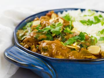 Close up of coconut chicken curry in blue bowl.