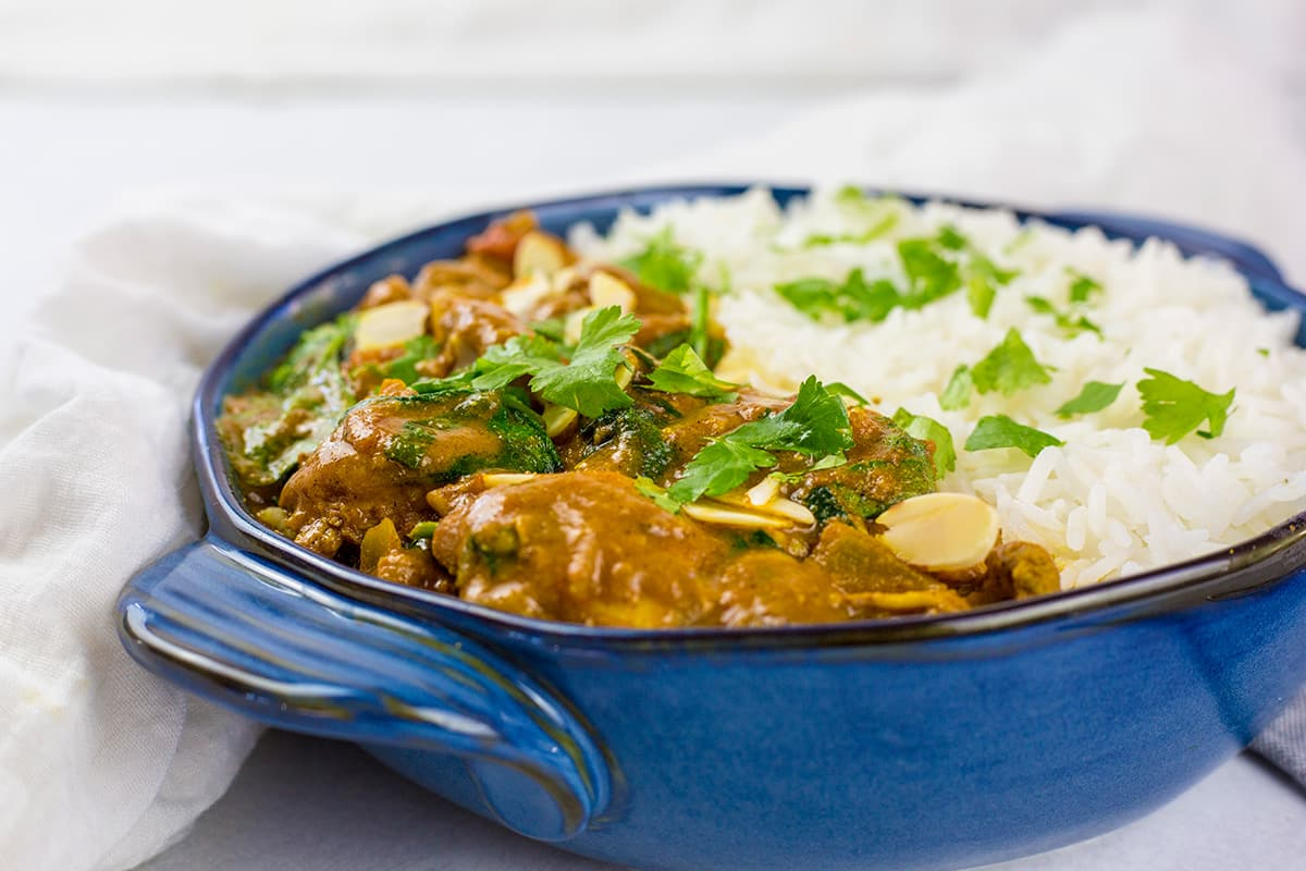 Close up of coconut chicken curry with rice in a blue bowl.