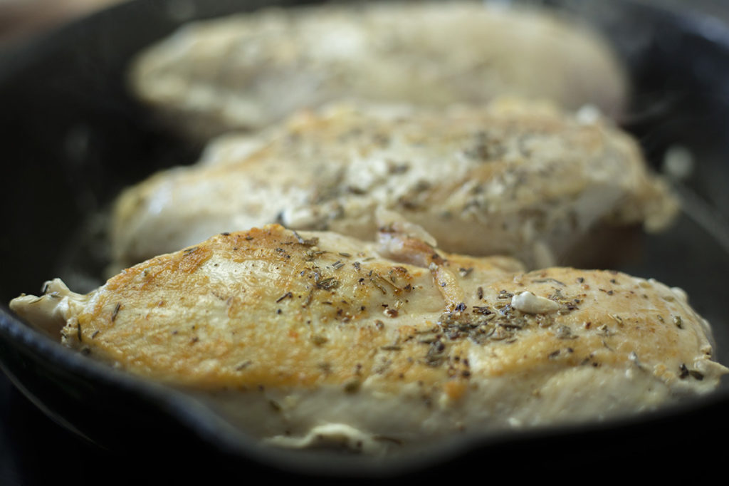 Process shot of chicken in frying pan being browned.