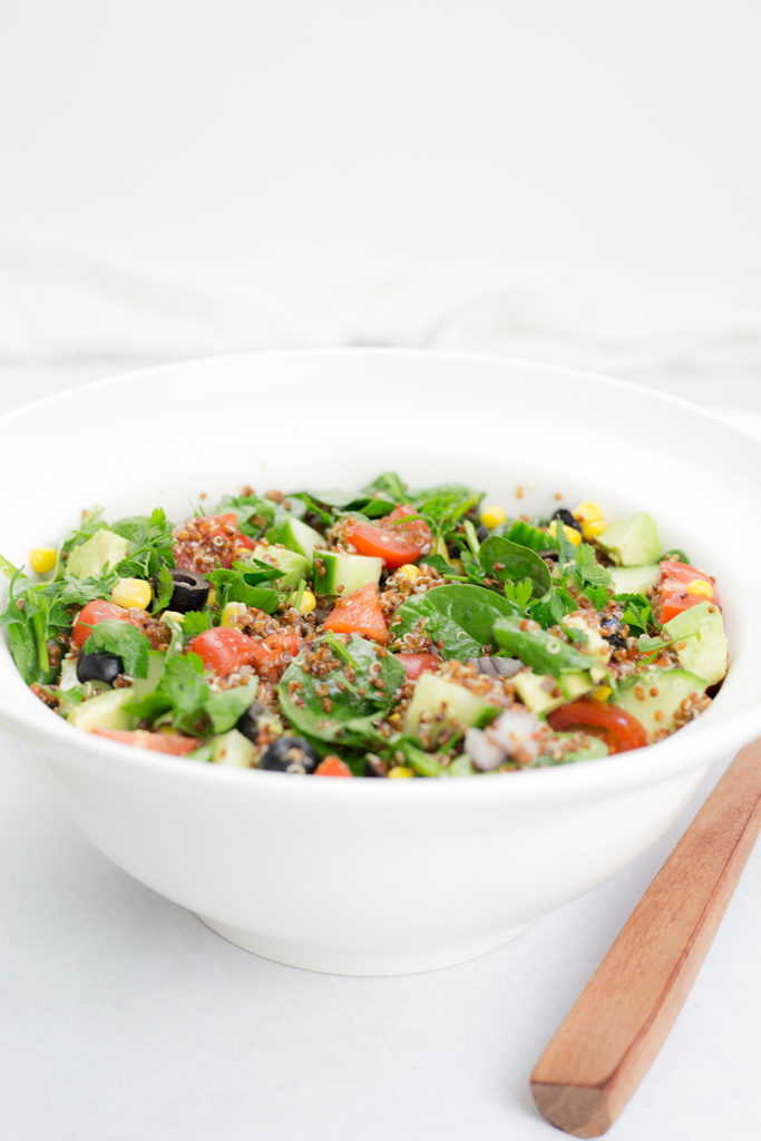 Vertical shot of quinoa salad with white background and end of serving spoon beside it
