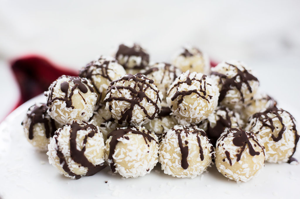 Close up of coconut almond snowballs with chocolate drizzle