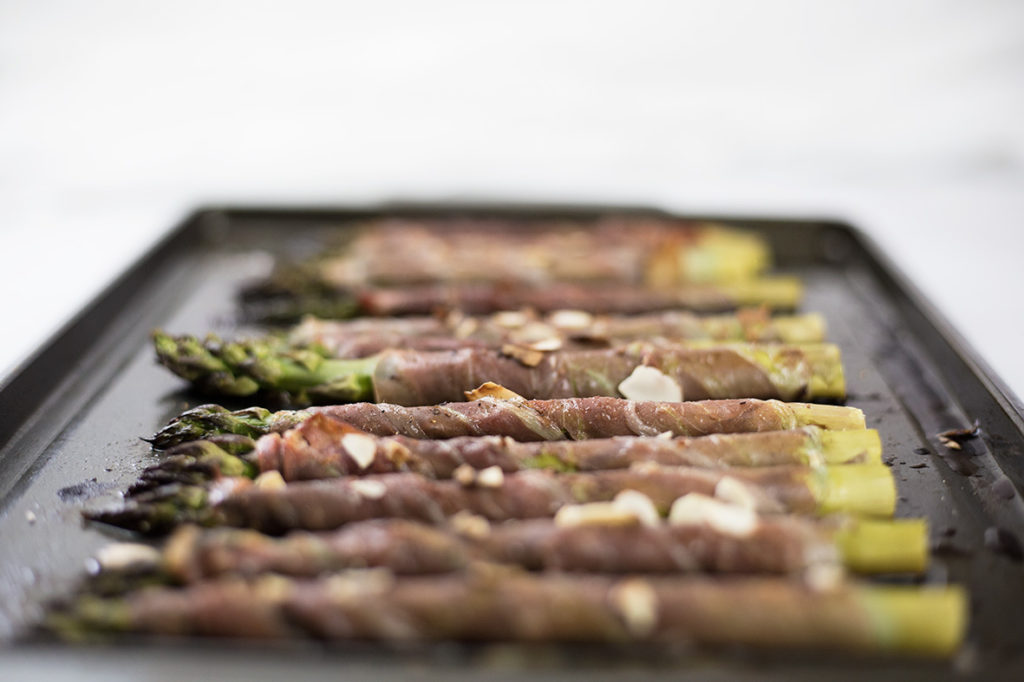 Prosciutto wrapped asparagus on baking tray