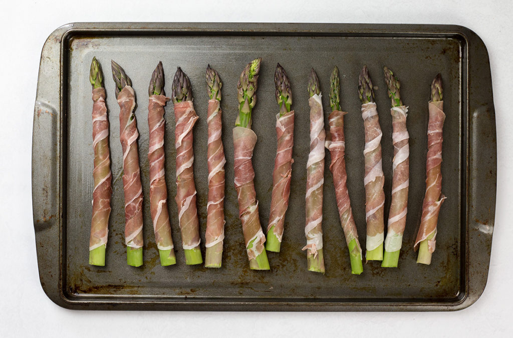 Prosciutto wrapped asparagus on baking tray ready to be prepared and go into oven