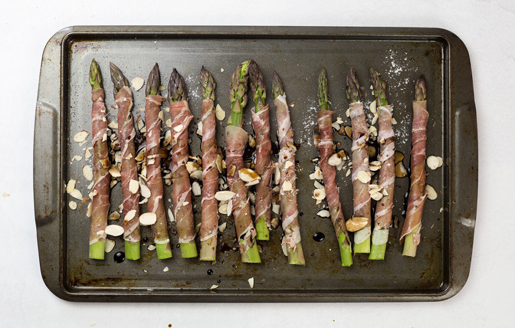 Birdsye view of prosciutto wrapped asparagus on tray with balsamic veingar drizzled on top with almonds