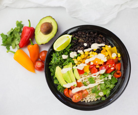 Birdseye view of vegan burrito bowl with avocado, red and orange pepper and coriander in background on a white backdrop.