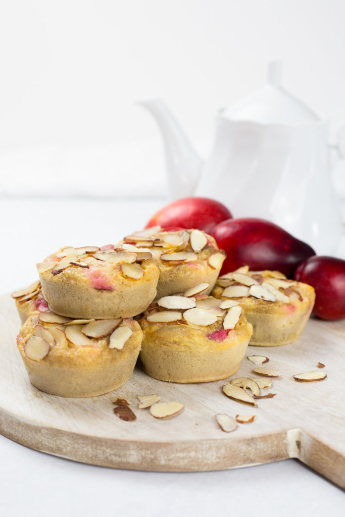 Vertical image of buckwheat plum muffins with teapot in background