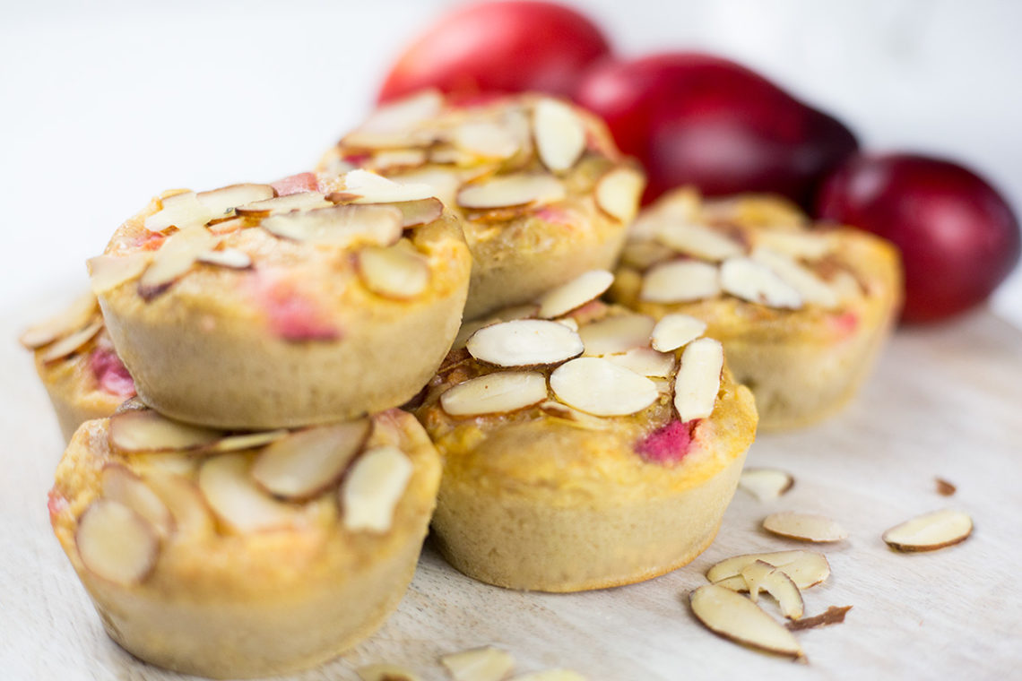 Close up of plum and almond buckwheat muffins on chopping board with plums in background