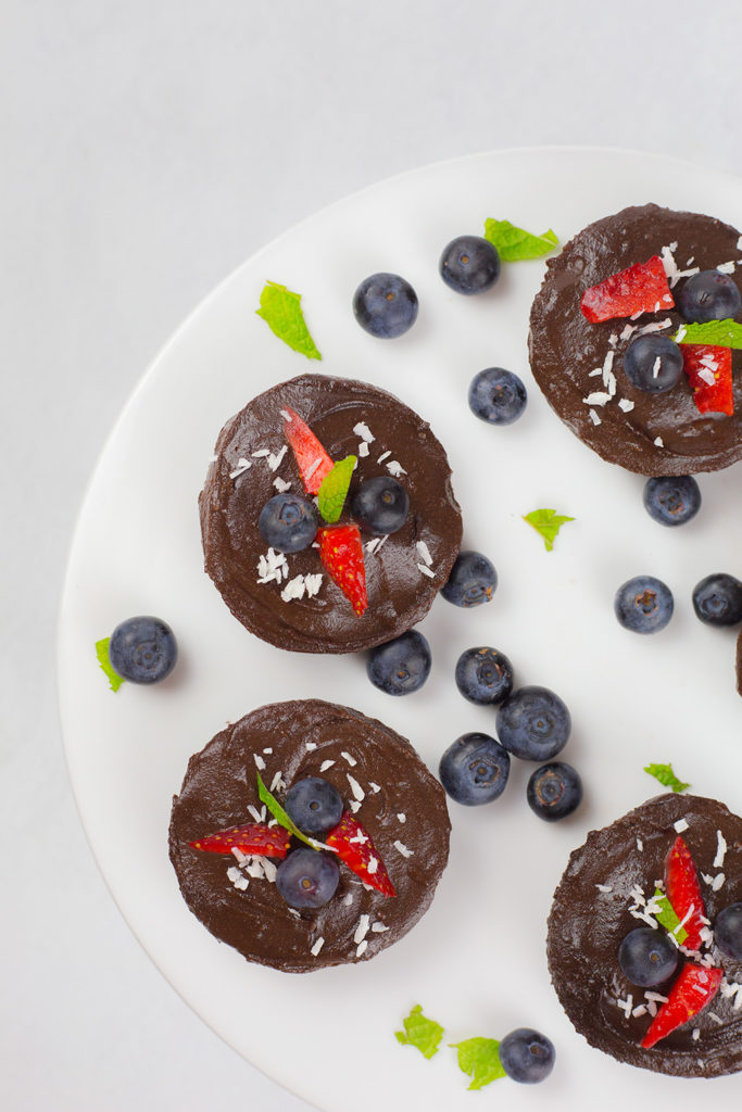 Birdseye view of no bake chocolate cheesecakes with blueberries, strawberries and mint