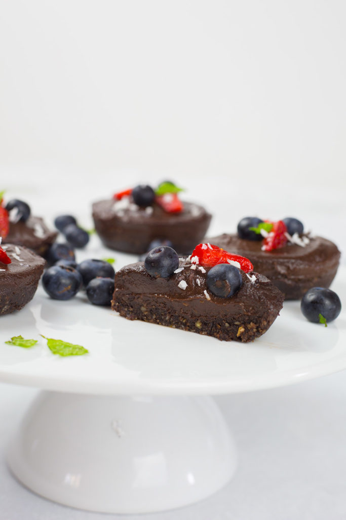 Dairy free chocolate cheesecakes on white platter with front one cut in half. Scattered with fruit and mint on top.