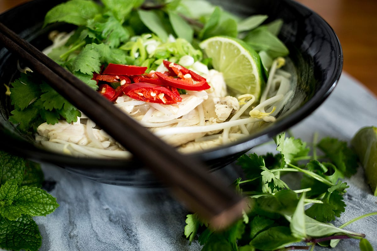Close up of chicken pho in black bowl with chopsticks on the left on marble background.