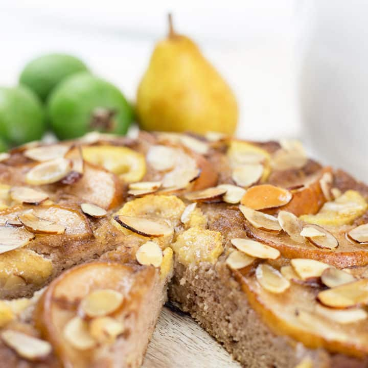 Close up of feijoa and pear cake with a slice removed on chopping board with fruit in background.