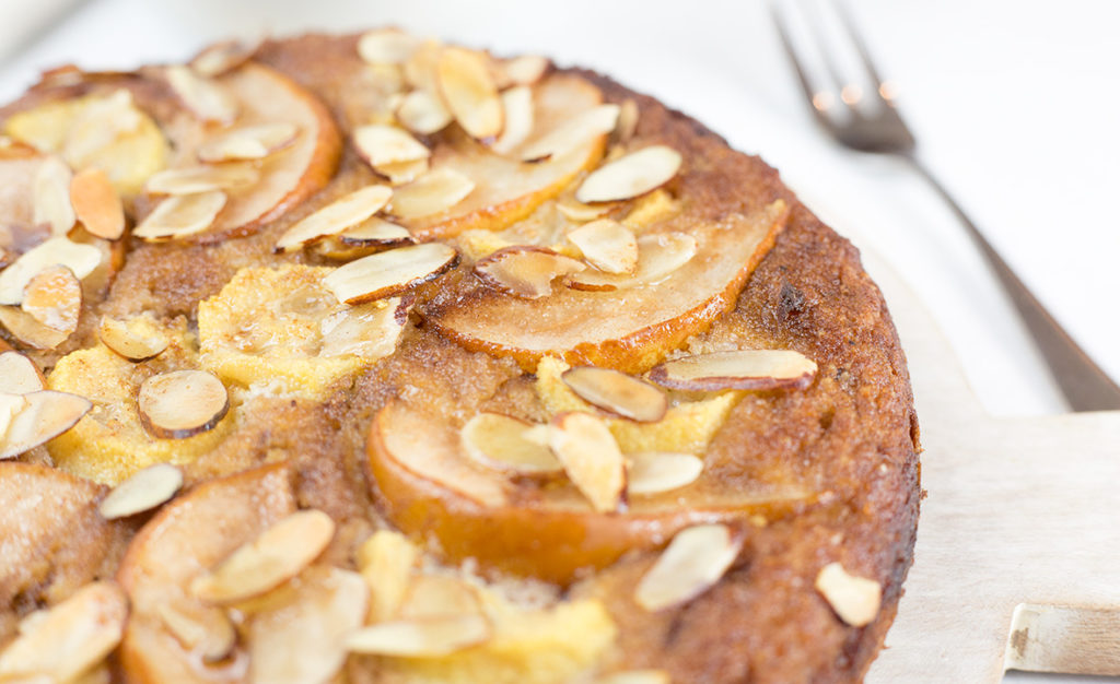 Close up of feijoa and pear cake on white background with fork to the right