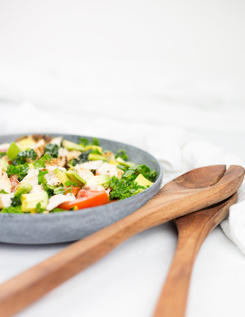 Veritcal photo of chicken salad on white background in a blue bowl with brown wooden serving spoons