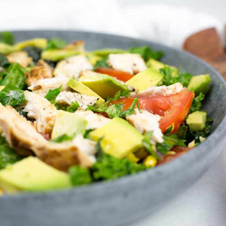 Close up of chicken salad on left with serving spoons on right, close up of chicken, avocado and tomatoes chopped in a bowl.