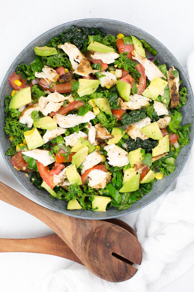 Close up of marinated chicken salad in blue/grey bowl with serving sppons. Shows lots of fresh vegetables such kale, avocado, tomato, corn.