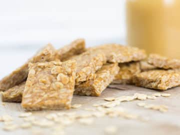Close up of peanut butter oat squares leaning on each other on a chopping board with honey in the background.