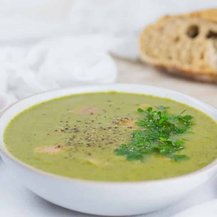 Pea and Ham Soup in a bowl with sliced bread on the side on chopping board.