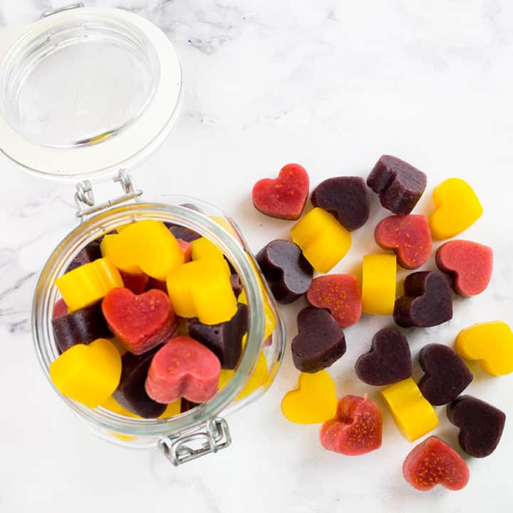 Birdseye view of gummies in jar with some outside of the jar on a marble background.