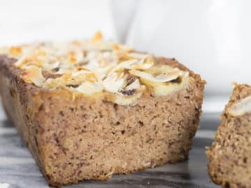 Close up of coconut banana bread slices, with shaved coconut on top and teapot behind it.