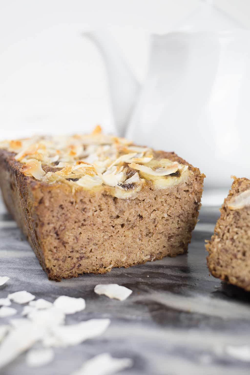 Coconut Banana Bread up close and sliced with teapot in background.