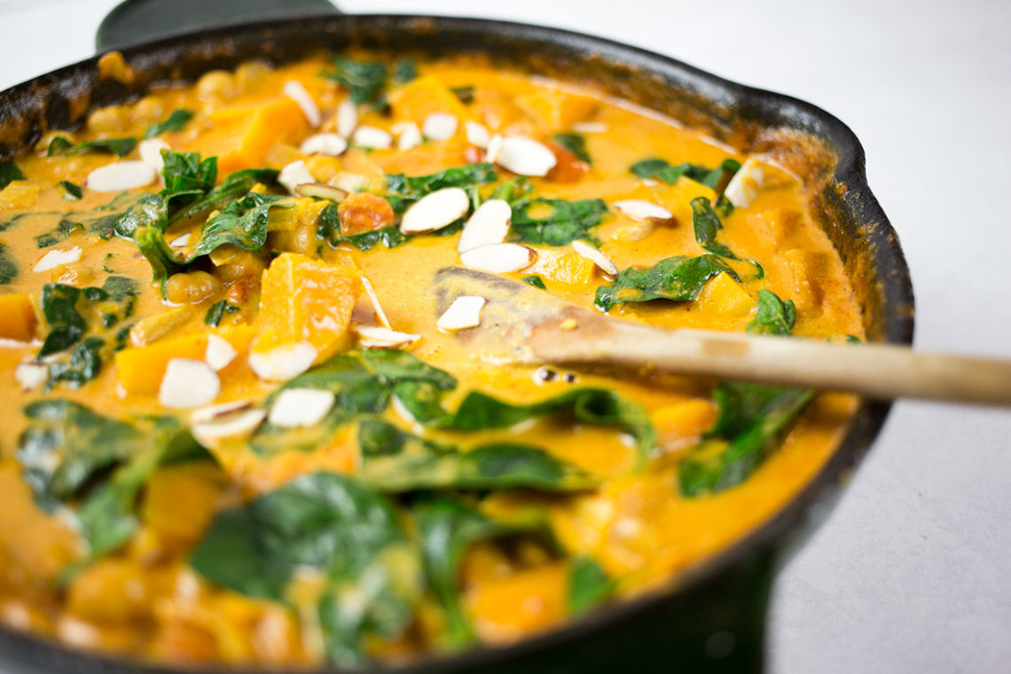 Close up of butternut squash and chickpea curry in black skillet with wooden spoon